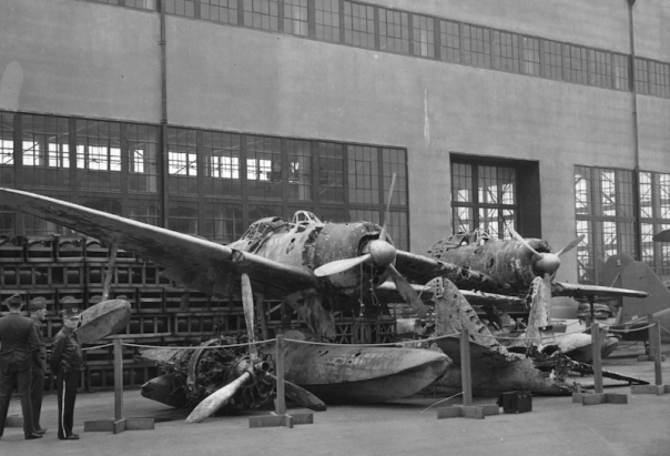 Wreck of a pontoon plane at NAS, 1947, with hangar in background